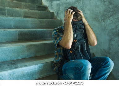 anti sexual discrimination and against homophobia campaign. Young sad and depressed college student man sitting on staircase desperate victim of harassment suffering bullying and abuse