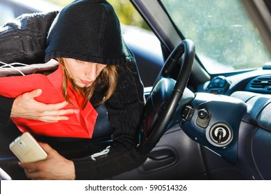 Anti theft system problem concept. Burglar thief man wearing black clothes breaking into car, stealing smartphone and red shopping bag