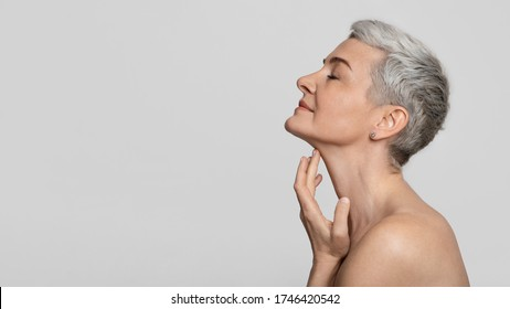 Anti-Age Treatment. Profile of beautiful middle-aged woman touching soft skin on her neck over light background, panorama with copy space