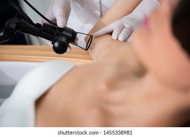 Anti-aging body treatment. Selective focus on cosmetologist making laser fractional resurfacing of inner side of upper arm while young woman lying on couch