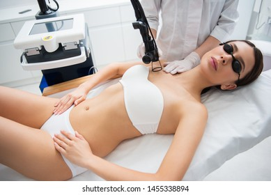 Anti-aging body treatment. Waist up top angle portrait of graceful young woman in white underwear and eyeglasses having laser fractional rejuvenation of decollete zone