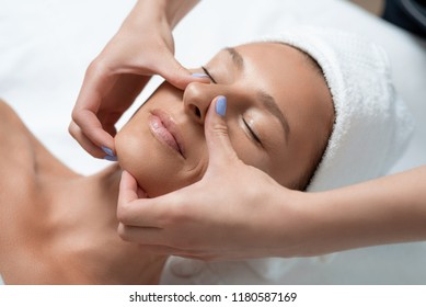 Anti-aging effect. Close up portrait of charming woman with closed eyes enjoying skincare procedure. Masseuse arms touching client chin and nose