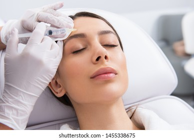 Anti-aging face treatment. Close up portrait of specialist making rejuvenation procedure of forehead by syringe to young careful woman lying on couch