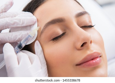 Anti-aging face treatment. Close up portrait of young smiling careful woman having rejuvenation procedure of forehead by specialist