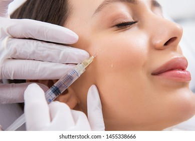 Anti-aging face treatment. Close up side on portrait of young smiling pretty woman relaxing on rejuvenation procedure of cheek bone zone by specialist