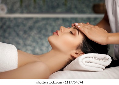 anti-aging facial massage. Woman receiving massage from masseur at Spa salon.