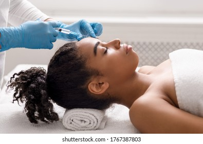 Anti-aging injections for attractive african american woman at spa salon