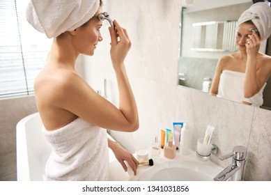 Anti-aging procedure for skin care. Waist up side on portrait of pretty smiling woman massaging face by Y-shaped ball roller before mirror after shower