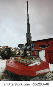 Anti-aircraft machine gun placed along with other weapons in the garden of an eccentrically decorated red-white townhouse in Nordmela-Andoya island-Lofoten Vesteralen islands-Nordland fylke-Norway.