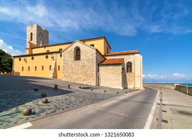 Antibes Cathedral on small town square and road along Mediterranean sea under beautiful blue sky in France.