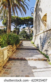 ANTIBES, FRANCE - 1st March, 2016: Cobblestone steps and a fort wall in Antibes, France surrounded by palm trees and exotic plants