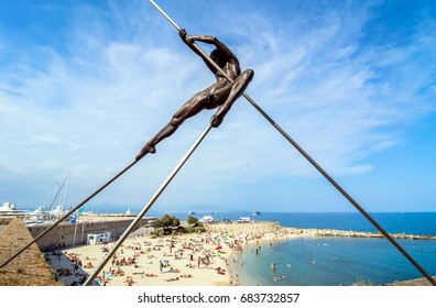 Antibes, France - July 01, 2016: day view of modern sculpture and Plage de la Gravette beach in Antibes. It is a popular local beach, a long stretch of fine, white sand at the end of the port.