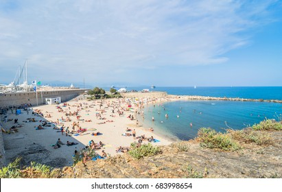 Antibes, France - July 01, 2016: people sunbathing on Plage de la Gravette in Antibes. It is a popular local beach, a stretch of fine, white sand at the end of the port.