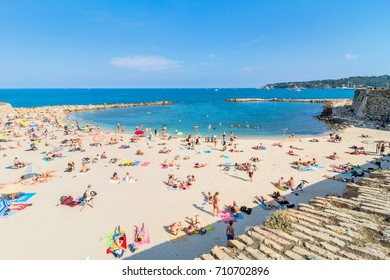 Antibes, France - July 01, 2016: people sunbathing on Plage de la Gravette in Antibes. It is a popular local beach, a long stretch of fine, white sand at the end of the port.
