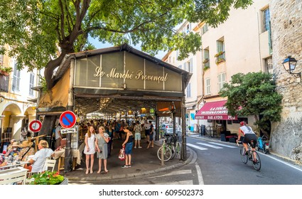 Antibes, France - June 29, 2016: day view of roofed market hall with unidentified tourists in Antibes, France. There take place a typical Provencal market with about 50 stalls.