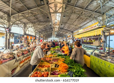 Antibes, France - June 29, 2016: day view of Cours Massena provencal market with tourists in Antibes, France. Antibes is a popular seaside town in the heart of the Cote d'Azur.