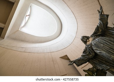 ANTIBES, FRANCE - MAY 14, 2016: Statue of Jesus Christ illuminated by the light from the top of the tower in the Modern style church of Sacre Coeur. It is built by Maurice HAURY between 1969 and 1972.