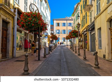 ANTIBES, FRANCE - SEPTEMBER 01, 2017: People walking on narrow street decorated with flowers in Old Town of Antibes - Mediterranean resort on Cote d'Azur in France, pupolar tourist destination.