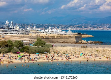 ANTIBES, FRANCE - SEPTEMBER 04, 2018: People on Plage de la Gravette - famous and popular sand beach near the Old Town as marina and luxury yachts on background in Antibes, France.