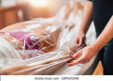 Anti-Cellulite-Baggertherapie für Arme und Beine. Weibliche Gäste liegen auf einem Massagetisch in einem Beauty-Wellness-Center, Arme und Beine in einer Nylontasche.