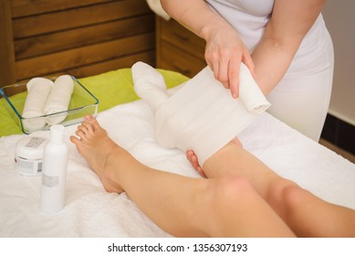 Anti-cellulite and cosmetologist STYX wraps procedure for legs in a spa center.