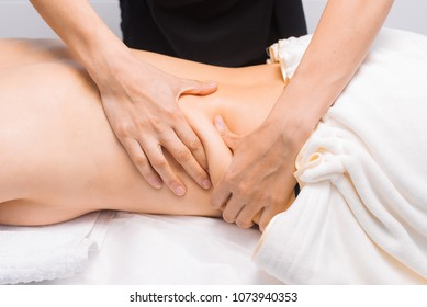 Anti-cellulite massage of thick sides. A professional masseur works in a massage room. Close-up. The technique of massage.