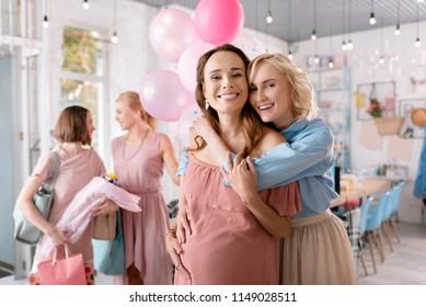 Anticipating girl. Smiling blonde-haired sister feeling so lovely while hugging her anticipating girl