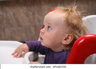 In anticipation of feeding baby sitting on a chair at a table