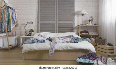 Anticipation of voyage. Women clothes and accessories mess up on bed in bedroom with suitcase on wooden floor. cozy room in apartment with unpacked luggage for summer holiday vacation concept.
