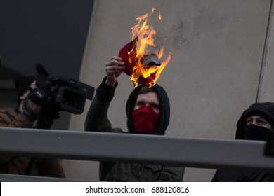 "An Anti-fascist demonstrator burns a red ""Make America Great Again"" hat outside the Inauguration of Donald Trump, Friday, January 20, 2017."