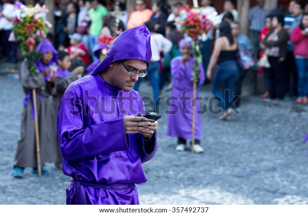 Antigua, 17 march 2015, Guatemala, A man dressed for a Religious procession uses his telephone