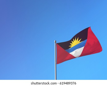 Antigua and Barbuda flag waving in the wind against a blue sky. 3D Rendering