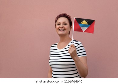 Antigua and Barbuda flag. Woman holding Antigua and Barbuda flag. Nice portrait of middle aged lady 40 50 years old with a national flag over pink wall on the street. Visit Caribbean islands