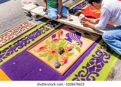 Antigua, Guatemala -  April 13, 2017: Decorating Holy Thursday dyed sawdust procession carpet in town with most famous Holy Week celebrations in Latin America