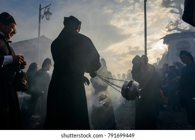Antigua, Guatemala - April 19, 2014: Silhouette of men wearing black robes and hoods spreading incense in a street of the city of Antigua during a procession of the Holy Week in Antigua, Guatemala