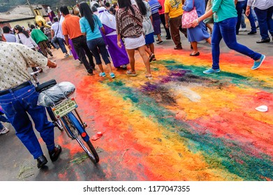 Antigua, Guatemala -  April 3, 2015: Locals follow Good Friday procession walking on trampled dyed sawdust carpet in UNESCO World Heritage Site with most famous Holy Week celebrations in Latin America
