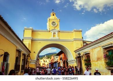 Antigua Guatemala, Guatemala / January 2, 2015: Tourists walk down 5a Avenida street under the Santa Catalina Arch, one of the town's main attractions.