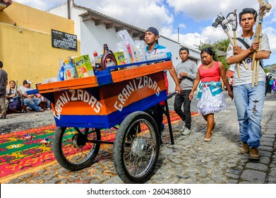 Antigua, Guatemala - Mar 1, 2015: Hobby horse & iced drink sellers walk past Lent processional carpet of dyed sawdust in town with most famous Holy Week celebrations in Latin America.