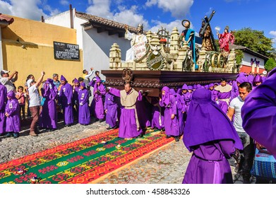 Antigua, Guatemala - Mar 1, 2015: Lent procession walks over dyed sawdust carpet in colonial town & UNESCO World Heritage Site with most famous Holy Week celebrations in Latin America.