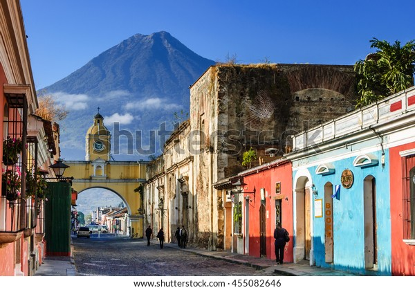 Antigua, Guatemala - March 11, 2012: Agua volcano behind Santa Catalina Arch (allowed nuns to pass to other side of convent without going outside) in colonial town & UNESCO World Heritage Site.