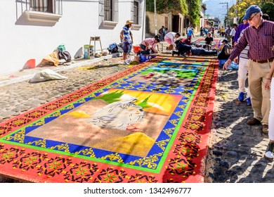 Antigua, Guatemala -  March 11, 2018: People admire dyed sawdust Lent carpets destroyed moments later by passing processions in town with famous Holy Week celebrations