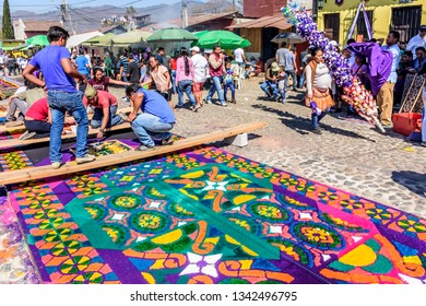Antigua, Guatemala -  March 11, 2018: Decorating dyed sawdust Lent carpet destroyed moments later by passing processions in town with famous Holy Week celebrations