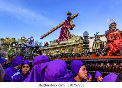 Antigua, Guatemala - March 15, 2015: Purple robed Catholic bearers (cucuruchos) carry float in Lent procession in Spanish colonial town with most famous Holy Week celebrations in Latin America.