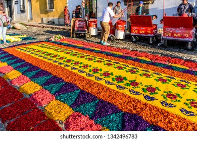 Antigua, Guatemala -  March 18, 2018: Drink sellers wait by dyed sawdust Lent carpet destroyed moments later by passing processions in town with famous Holy Week celebrations