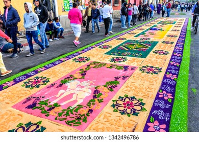 Antigua, Guatemala -  March 18, 2018: People walk past admiring dyed sawdust Lent carpet destroyed moments later by passing processions in town with famous Holy Week celebrations