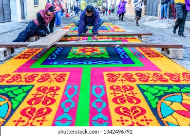Antigua, Guatemala -  March 18, 2018: Decorating dyed sawdust Lent carpet destroyed moments later by passing processions in town with famous Holy Week celebrations