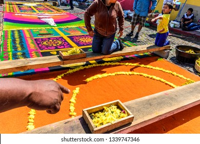 Antigua, Guatemala -  March 25, 2018: Decorating dyed sawdust Palm Sunday  carpet with flowers destroyed moments later by passing processions in town with famous Holy Week celebrations