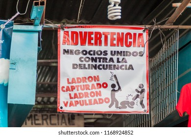 ANTIGUA, GUATEMALA - MARCH 27, 2016: Warning sign at the market in Antigua Guatemala city. It says: Warning. United enterprises against delinquency. Captured thief, beaten thief.