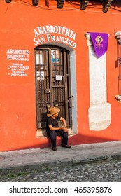 ANTIGUA, GUATEMALA - MARCH 27, 2016: Local man sits at the doorway of a colorful colonial house in Antigua, Guatemala
