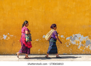 ANTIGUA, GUATEMALA - MARCH 28 2013: Street view with indigenous Mayan women in traditional clothing near the handicrafts market of Antigua.